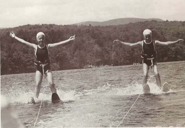 Two young girls waterskiing